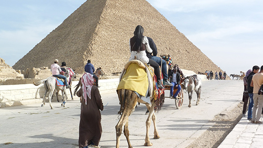 A pyramid and tourists riding camilles