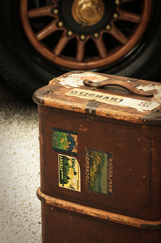 An old luggage with postcards stuck to it, and a tire in the background