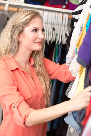 women looking up at clothes in closet