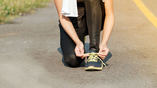 woman in middle of road tying shoes
