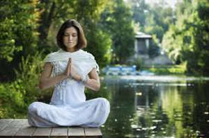 Woman meditating near lake
