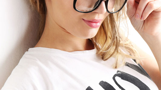 young woman wearing black eye glasses and white shirt with something written on it
