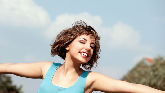 girl in light blue tank tops smiling with arms wide open