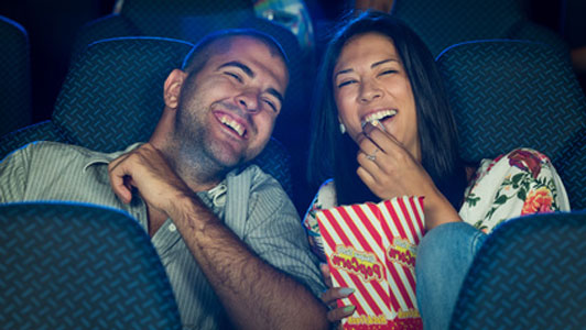 happy couple at movie eating popcorn