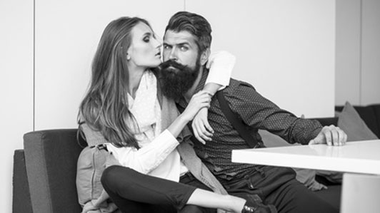 black and white photo of bearded man with arm of woman around him on couch in front of table