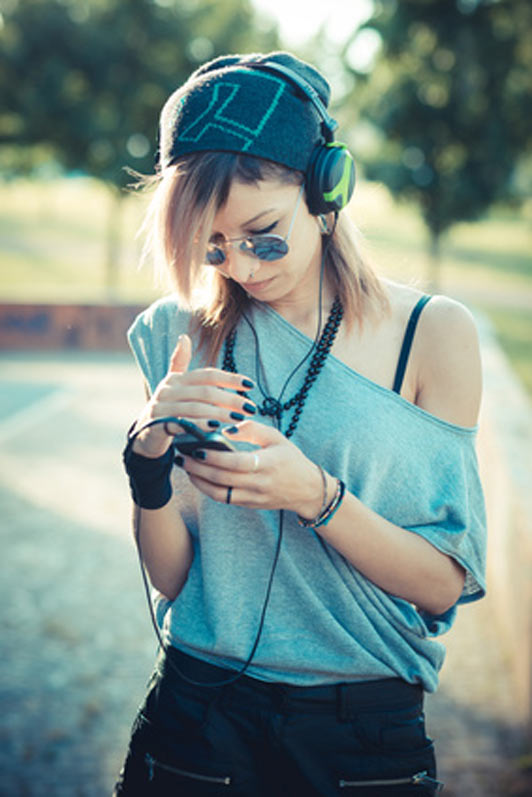 young beautiful model woman listening to music outdoors