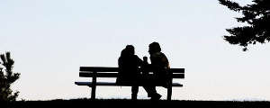 Two people sitting on a bench.