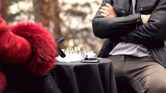 Woman with red fur playing glass chess with a guy