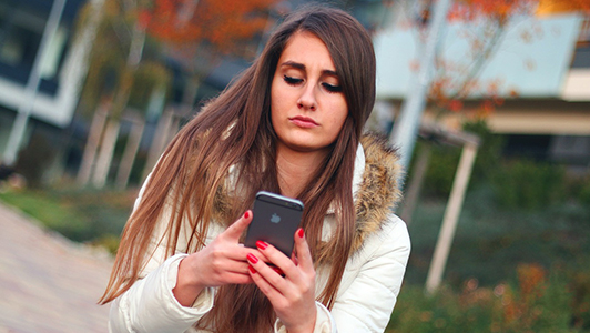 Girl with long hair texting on an iPhone