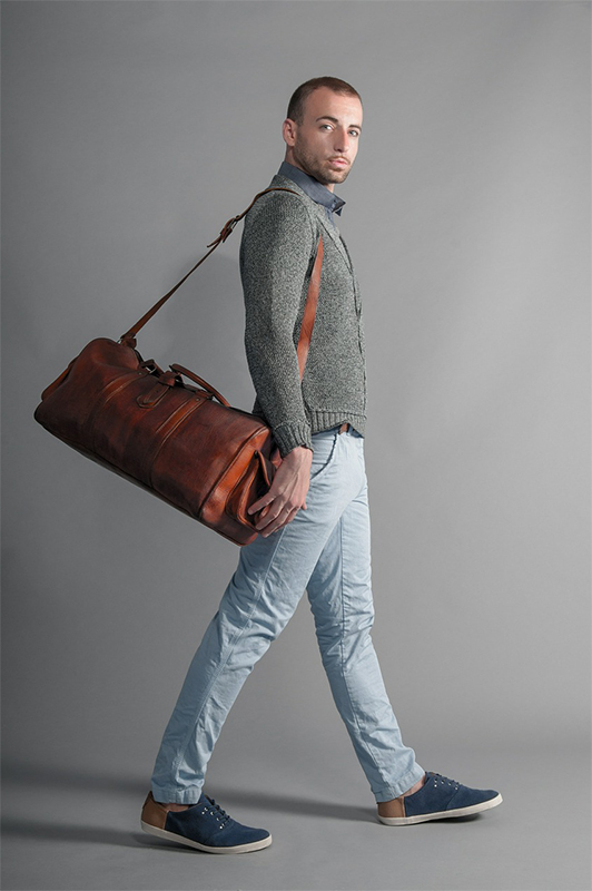 Guy in a sweater carrying a brown bag.