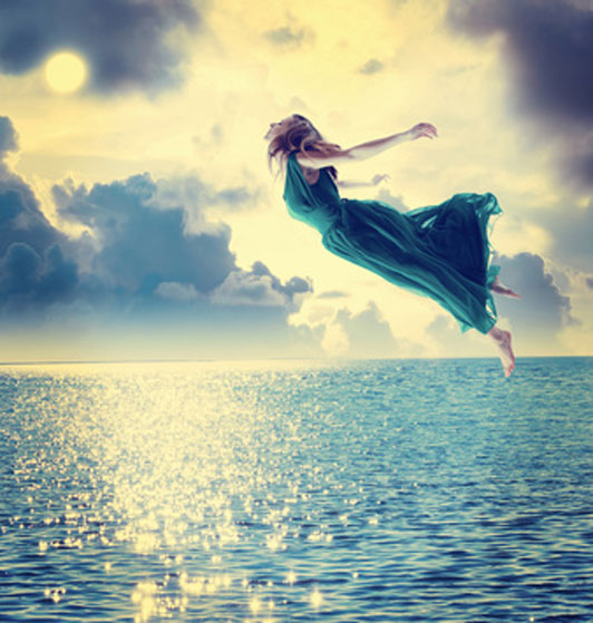 woman in blue dress flying into sunset over ocean