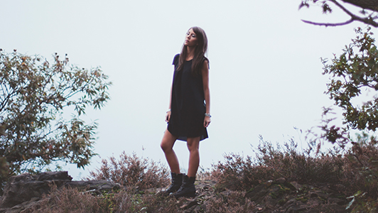 Girl in black dress and boots standing near a bush.