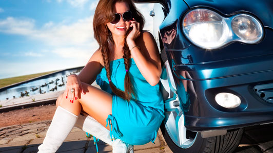 stylish girl hiding behind luxury vehicle