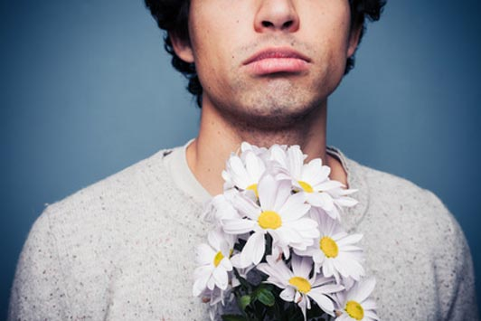 sad guy holding flowers after rejection