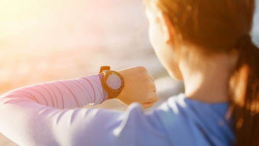 woman looking down at watch checking time