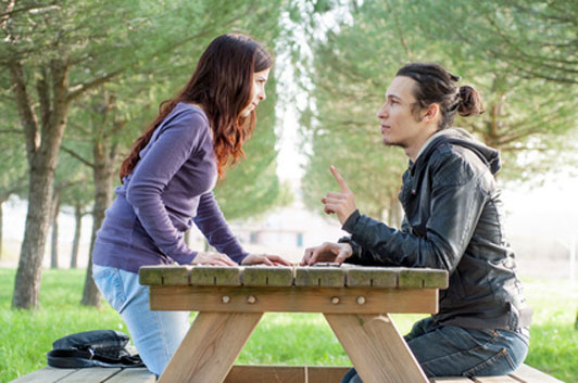 guy and girl in middle of a fight sitting on a park bench; quarrel of love