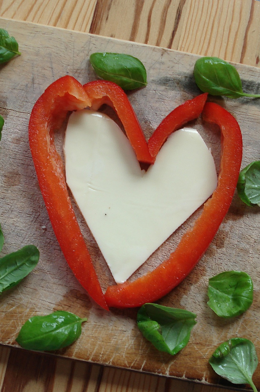 Heart made of paprika and cheese, with herbs sprinkled around.