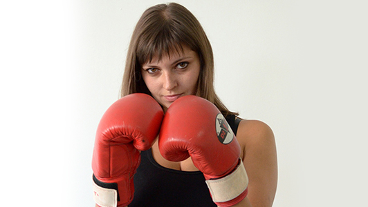 Girl in black top wearing boxing gloves.