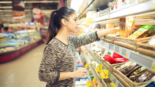 woman checking supermarket shelf