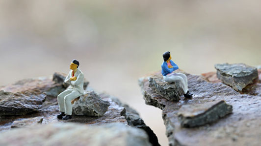 two people in disagreement sitting on rocks