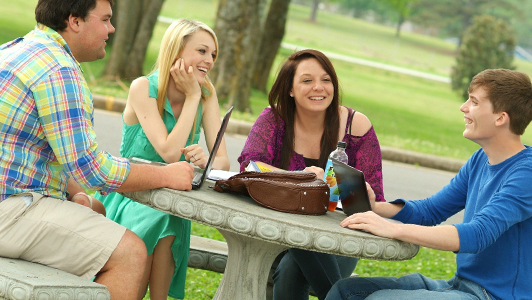 young people talking around table outdoors