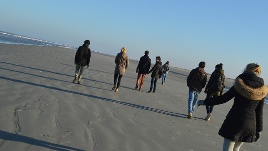 Girl in a jacket walking behind a group of people on a beach.