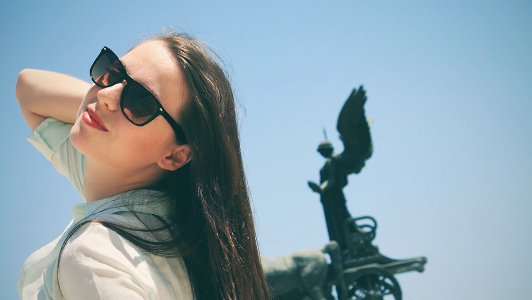 Girl with long hair and sunglasses smiling.