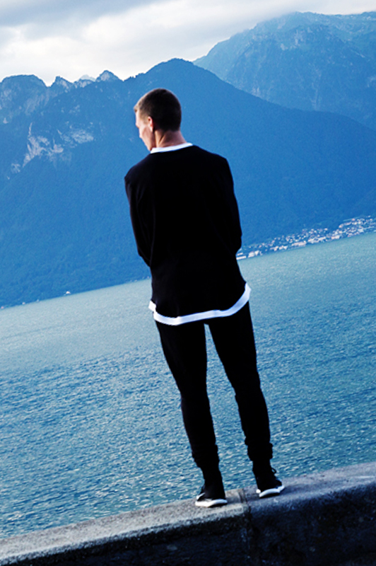 Guy standing on the edge of a wall looking at a lake.