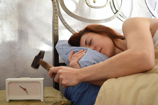 sleep deprived woman holding hammer to break alarm clock