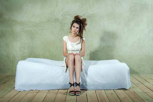 tired woman with messy hair sitting on lone bed