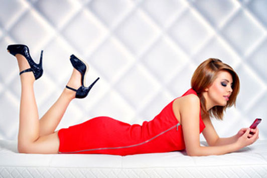 woman in red clothes and black high hills on bed with phone