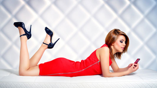 young woman in red dress and black high heels lying on stomach holding phone