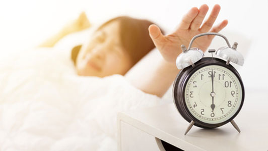 girl waking up reaching for alarm clock