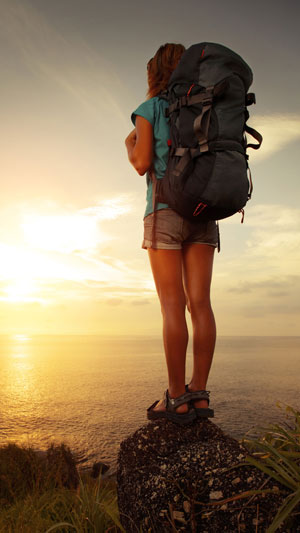 Girl with a backpack watching sunset.