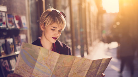 traveling woman looking over map in street