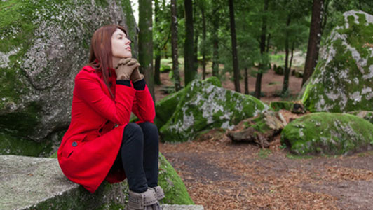 woman in red coat waiting on stone table alone