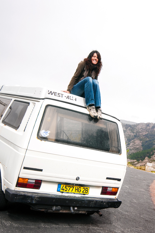 Girl sitting on top of a van.