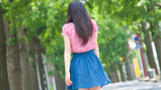 girl in short-sleeve and blue skirt walking outdoors