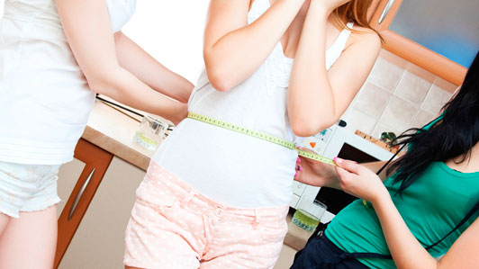 midsection of girl being measured by two other girls