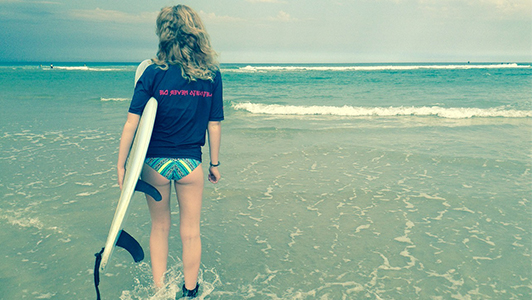Girl in a tee with a surfing board