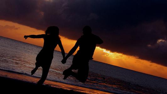A couple jumping on a beach
