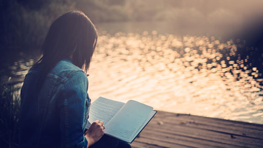 young woman reading lakeside