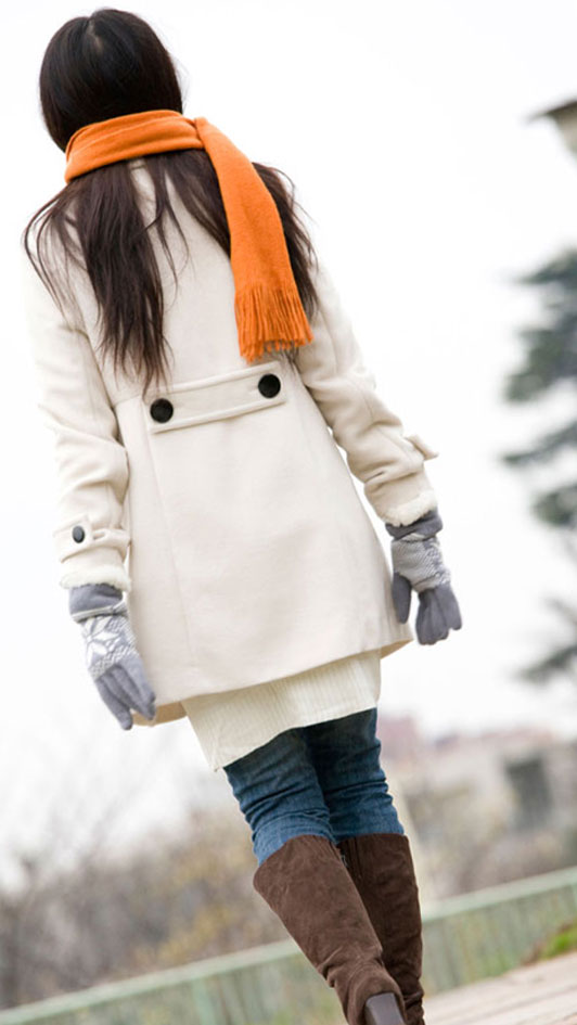 girl in orange scarf walking alone outdoors