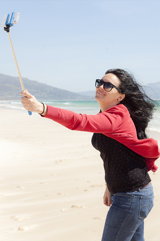 Woman taking a selfie using a selfie stick.