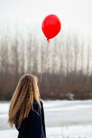 woman holding red balloon