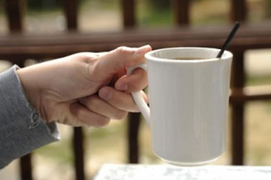 hand of woman holding white mug