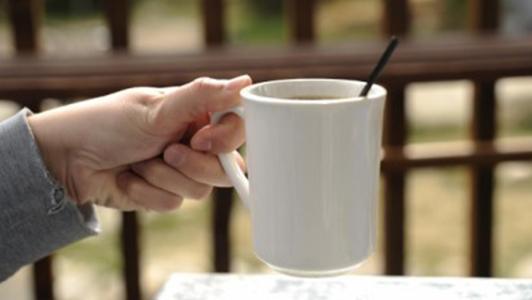 A hand holding a white mug