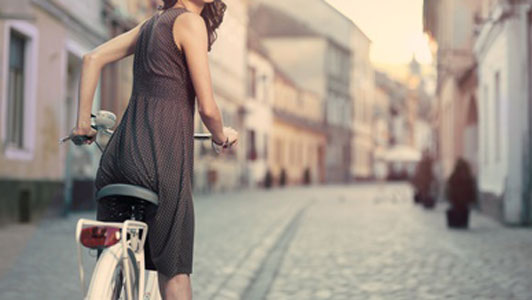 woman in brown dress with polka dots on bicycle