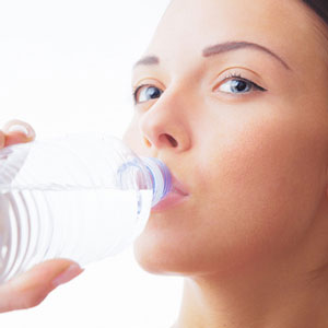 close up on face of woman drinking water