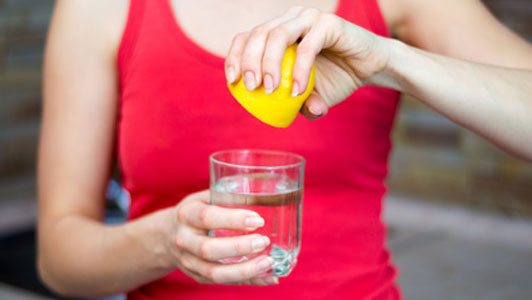 woman in red tank top squeezing lemon into water